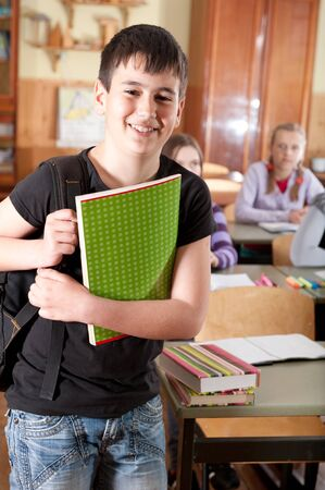Smiling schoolboy with notebook in front of class Stock Photo