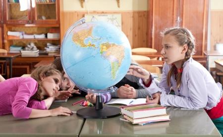 schoolkid search: Los escolares est�n explorando mundo en el aula durante la lecci�n Foto de archivo