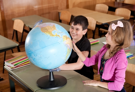 Schoolchildren are exploring globe in classroom during lesson photo