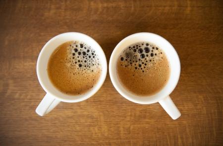 tazas de cafe: Dos tazas de café espresso en whte con mesa de madera