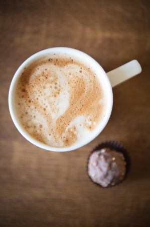 Heart shape on latte over wooden table photo