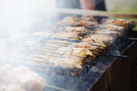 Juicy chicken meat in grates and smoke during barbecue photo