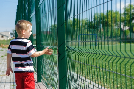 sad people: Little boy standing outisde of sportfield near grid fence