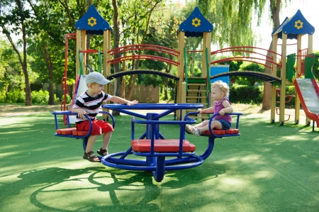roundabout: Little brother and sister spinning on roundabout at playground Stock Photo