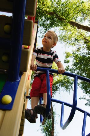 Little cute boy is climbing at playground photo