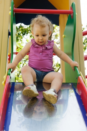 Curly haired blonde little girl at playground Stock Photo - 14774664