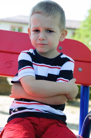 Serious little boy with negative emotons sitting at playground photo