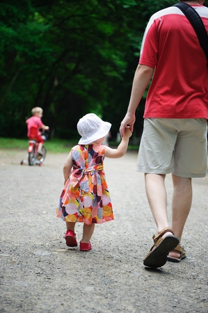 kids holding hands: Young father and his little daughter walking in the park. Little  son is riding a bicycle
