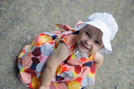 Cute baby girl in white hat sitting in park photo
