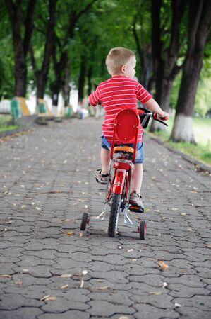 Niño de cuatro años andando en bicicleta en el parque. Vista trasera. Foto de archivo - 14774686