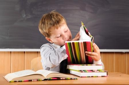 diligente: Lindo chico de primaria se sienta en el escritorio con libros