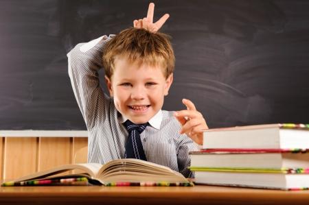 Lindo chico de primaria engañando a la lección Foto de archivo