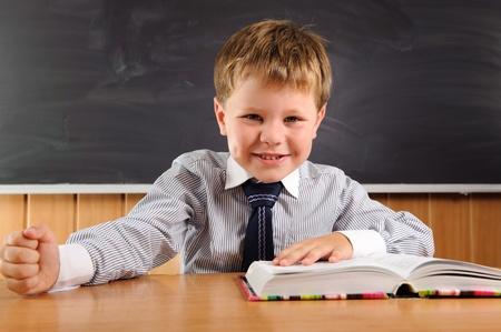 convivencia escolar: Confiado colegial elemental edad sentado en el escritorio Foto de archivo