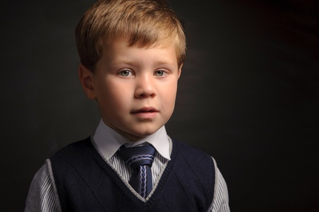 Cute pupil portrait against dark classroom blackboard photo