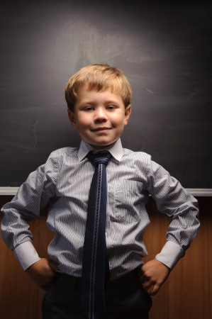 Cute preschooler against dark blackboard in classroom photo