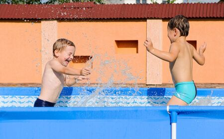 Two excited boys splashing in swimming pool photo