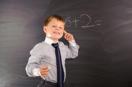 preschool classroom: Cute preschooler against dark blackboard in classroom