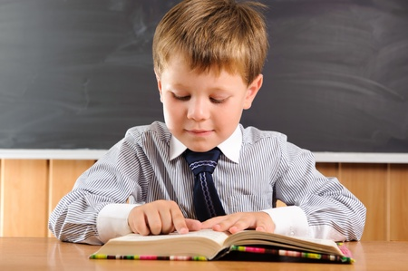 Cute elementary aged boy sitting at the desk with books photo
