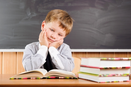 Tired elementary aged boy sitting at the desk with books photo