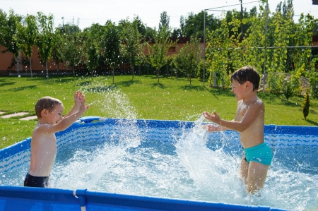 Two excited boys splashing in swimming pool Stock Photo