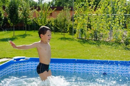 Cute boy jumpong in a pool at the garden photo