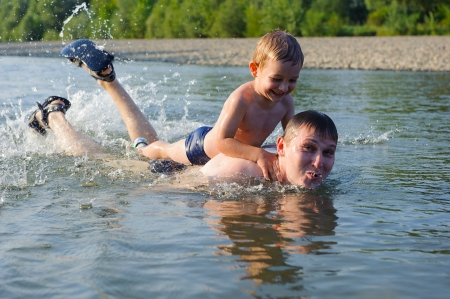Young father and his little son swimming in river photo