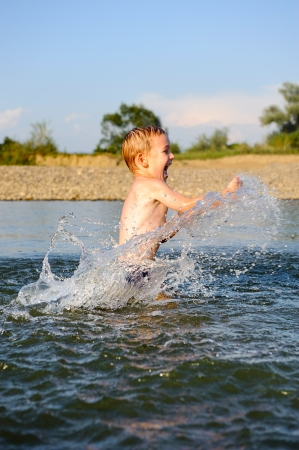 Little boy is splashing water in river photo