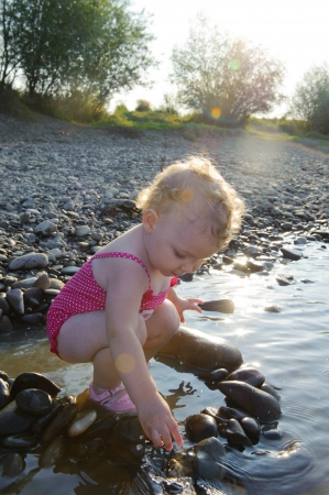 Cute baby girl playing with stones on river photo