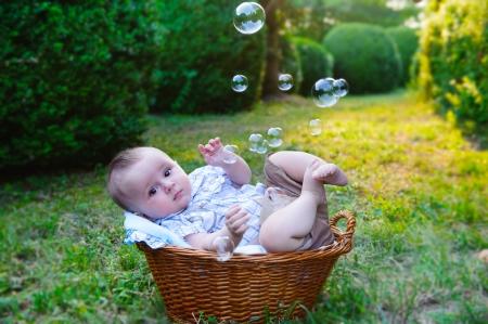 Cute little boy lying in basket in the park