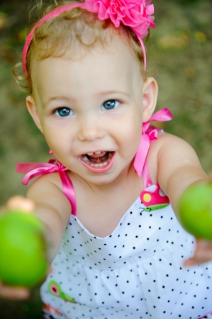 hair band: Cute little girl gives green apples sincerely