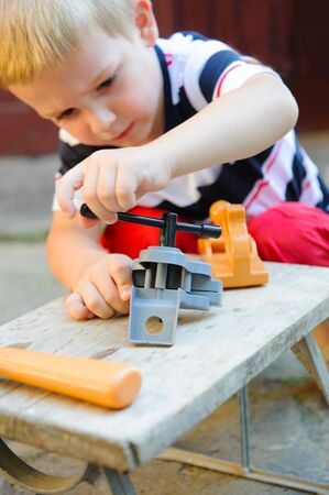 concentrating: Concentrated little boy is playing in carpenter