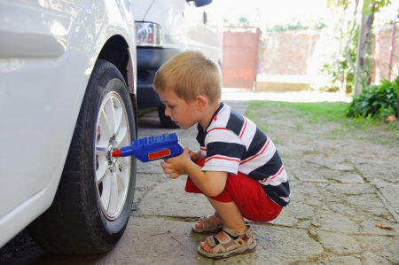funny car: Cute child repairing alloy wheel of a real car