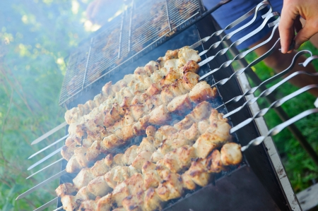 Barbecue closeup. Shashlik on foreground and grid in background photo