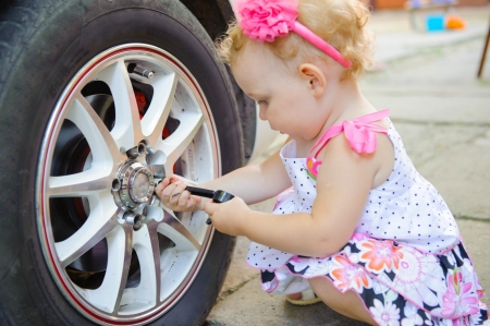 Cute girl with head band repairing alloy wheel of a real car photo