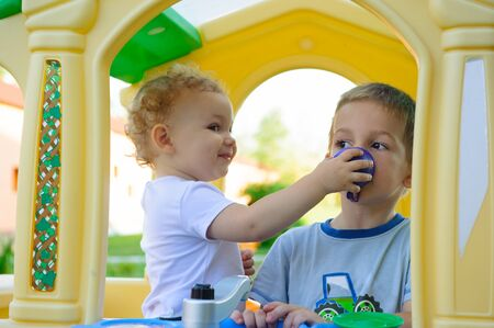 Cute little girl feeding his brother outdoors photo