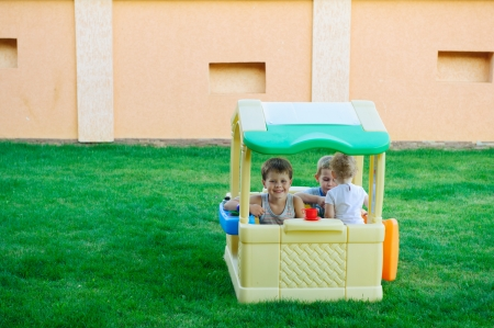 Children playing in toy house at playground Stock Photo - 15214070