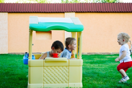 Children playing in toy house at playground photo