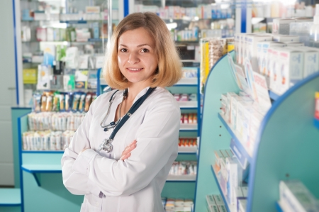 Young pharmacist with phonendoscope in drugstore photo