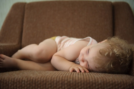 Curly haired blonde baby girl sleeping on armchair photo