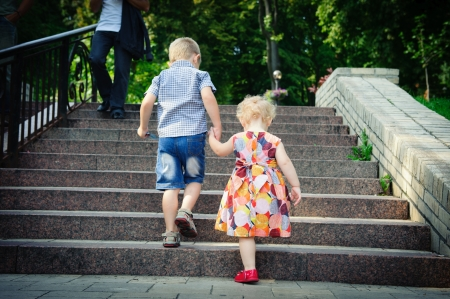 Brother aged four and sister aged two walking in park photo