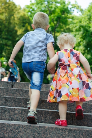 stone stairs: Brother aged four and sister aged two walking in park