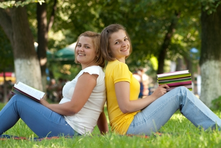 Two female students studying at campus park photo