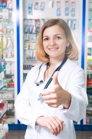 Young smiling druggist in pharmacy store with thumb up photo