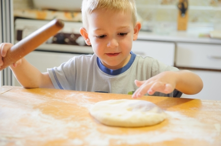 little dough: Little boy rolling dough in the kitchen Stock Photo