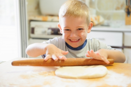 Little boy rolling dough in the kitchen photo