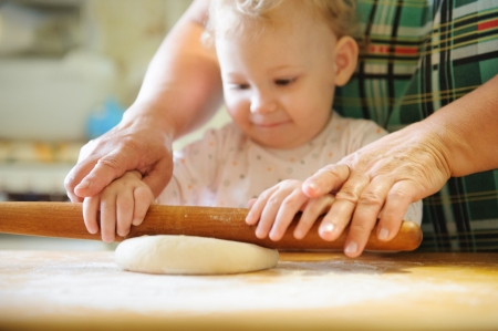 little dough: Baby girl rolling dough with her mother