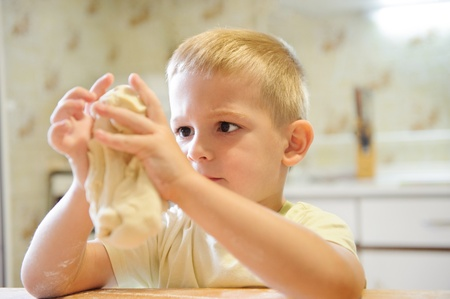 Concentrated little boy kneading dough in the kitchen photo