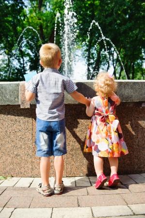 Kleiner Bruder und Schwester auf den Zehen suchen am Brunnen