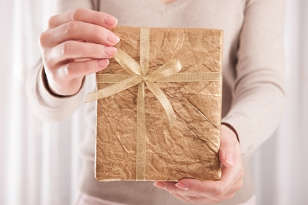 Young woman holding Christmas present box wrapped in golden paper Stock Photo - 15705062