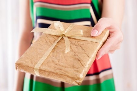 Young woman holding Christmas present box wrapped in golden paper photo